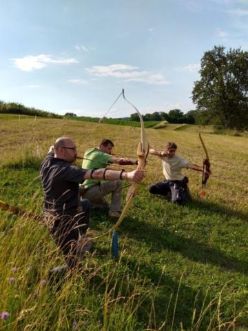 Drei Bogenschützen schießen knieend