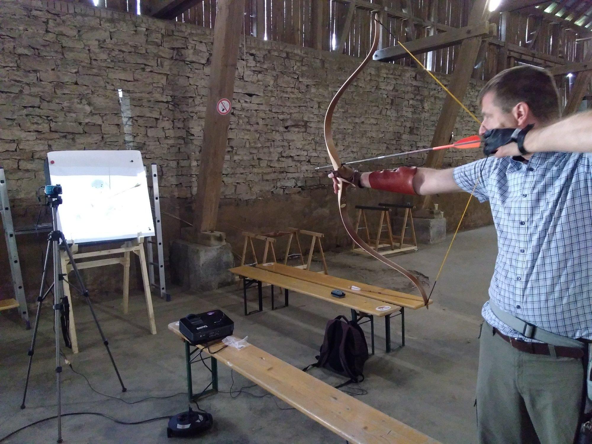 Bogenschütze im Training mit Unterstützung eines Beamers